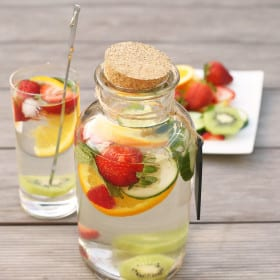 Super healthy Flavored Fruit Water infused with sliced strawberries, orange slices, cucumber, mint and kiwi. The perfect refreshing drink on a warm day! No artificial ingredients added. #fruitwater #fruit #drink #strawberries #oranges #cucumbers #water #healthy #vegan #detox