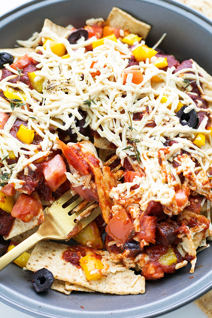 Vegan Pizza Nachos - a combination of Pizza Toppings and Tortilla Crisps, baked to perfection. #vegan #pizza #nachos #fusion #cheese #chips