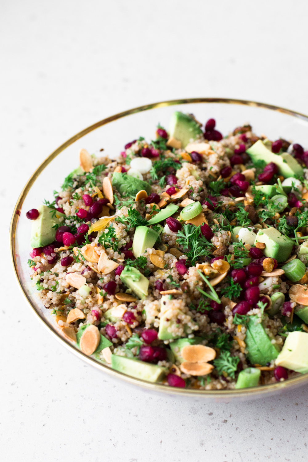 A delicious Vegan Quinoa Crunch Salad studded with toasted Almond, Pistachio and Pomegranate. Perfect for a healthy lunch or as a potluck dish! #quinoa #christmas #holidays #pomegranate #orange #healthy #glutenfree #salad #avocado #pistachio #almond