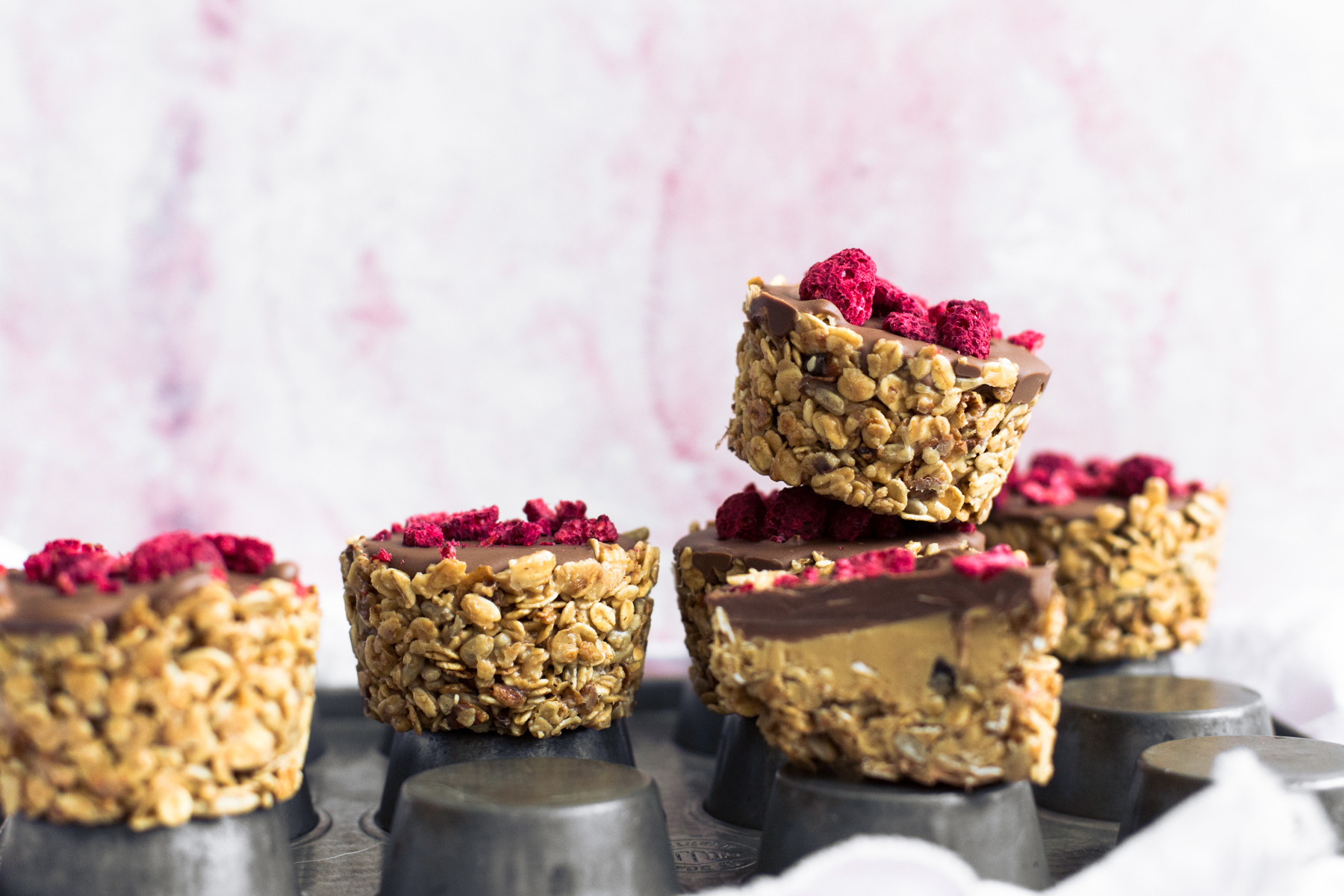 Simple No-Bake Vegan Granola Cups filled with Nut Butter of your choice and topped off with Chocolate. Read in under an hour. #vegan #granola #oats #chocolate #snacks #healthy #peanutbutter #nobake #slice #fridge #veganrecipes