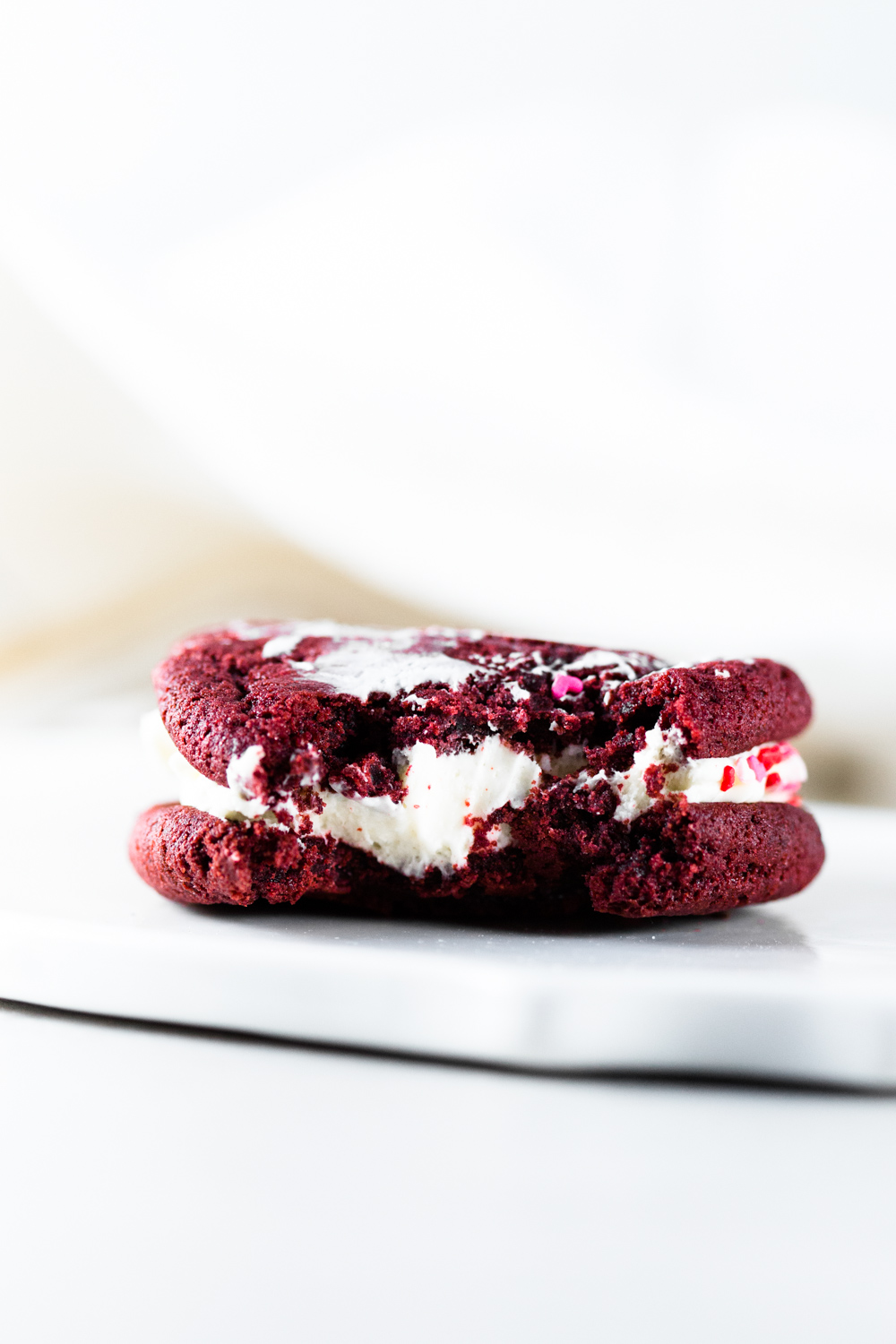 Delicious and chewy Vegan Red Velvet Cookies sandwiched with a yummy Cream Cheese Frosting. Think Red Velvet Cake, but in a convenient cookie form! #redvelvet #cookies #veganredvelvet #vegancookies #cheesecake #creamcheese #icing #dairyfree #eggless #cake #simple #easy #baking