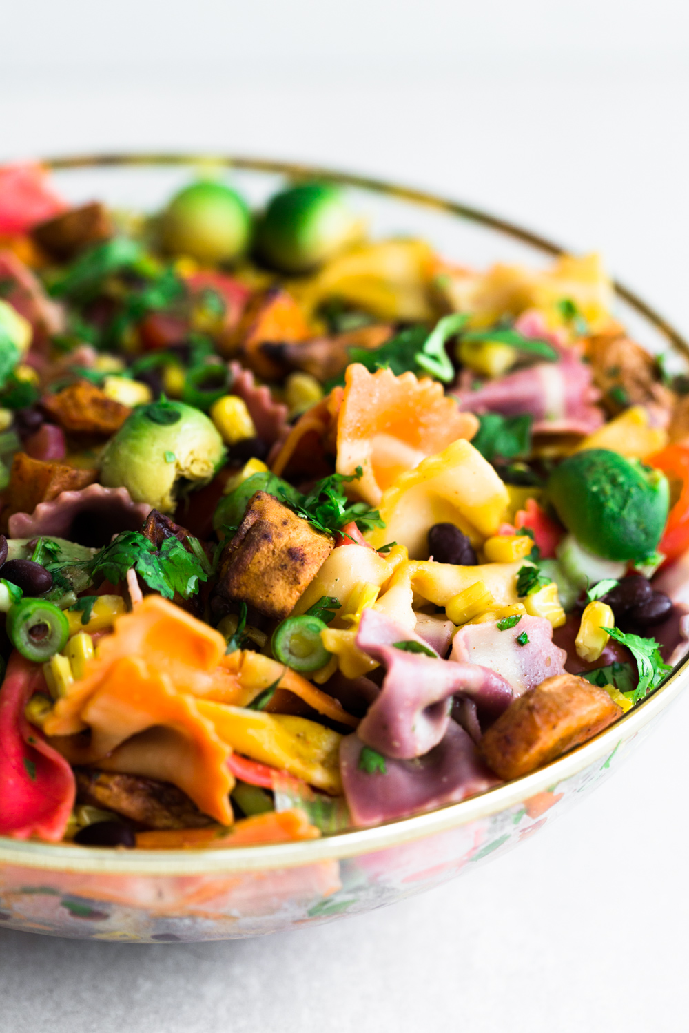 A Mexican inspired Vegan Southwestern Pasta Salad with Roasted Sweet Potato, Grilled Corn, Cherry Tomatoes, Black Beans & a Cumin Lime Vinaigrette. #healthy #vegan #pasta #salad #southwestern #mexican #corn #rainbow #salad #vegetarian #healthyrecipe