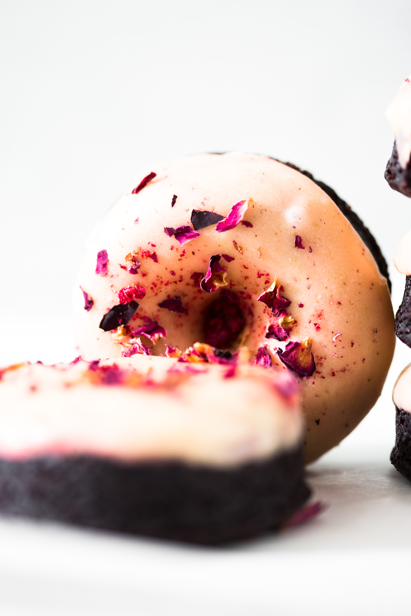Moist and delicious Vegan Baked Chocolate Donuts topped with a floral Rose Glaze. Easy to make and ready in under 30 minutes. #donuts #vegandonuts #cakedonuts #bakeddonuts #turkishdelight #chocolate #chocolatedonuts #baking #vegetarian #chocolatecake #easy #30minutes